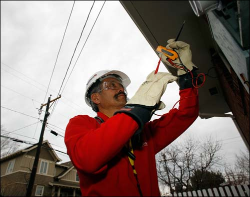 Gary Kawano installs a new meter outside a home in Boulder, Colo., Nov. 25, as part of the smart electrical grid system being put into place in the city. The energy secretary plans to roll out support to such programs as soon as possible.  AP Photo by David Zalubowski