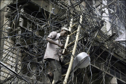 In this June 13 file photo, an electrical linesman repairs cables in the middle of a spider web of  illegal subsidiary wires around the main cables in Allahabad, India. Stealing of power is a frequent phenomenon in Indian towns.