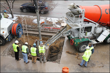Workers with D.F. Tomasini Contractors Inc., Sussex, as well as inspectors and concrete subcontractors, view a concrete pour along East Capitol Drive in Shorewood. Tomasini was repairing a damaged sanitary sewer. (Photo by John Krejci)