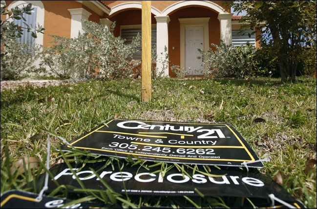 A sign lies on the ground in front of a foreclosed home in Homestead, Fla. Officials in 50 states have launched a joint investigation into allegations that mortgage companies mishandled documents and broke laws in foreclosing on hundreds of thousands of homeowners. (AP File Photo/J Pat Carter)