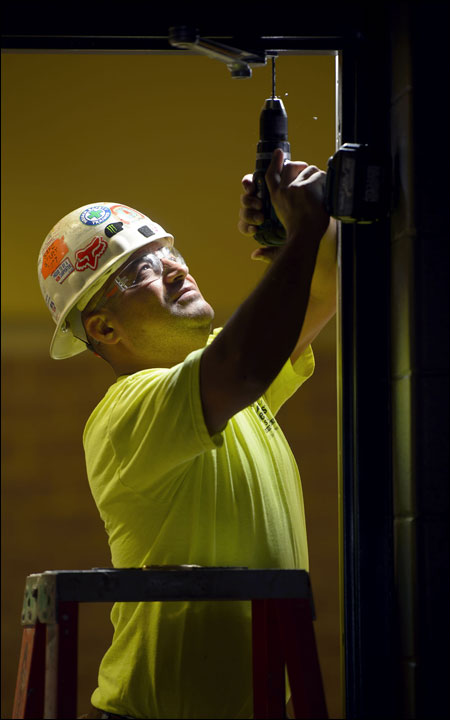 Jose Diego of Hunzinger Construction Co., Brookfield, installs hardware for a door in an auditorium under construction Sept. 19 at Pewaukee High School. Hunzinger is the general contractor on the ongoing expansion project at the school that includes classrooms, a new 23,000-square-foot gymnasium, a 16,000 square-foot cafeteria expansion, a new 750-seat auditorium, and the renovation of several existing areas within the school. The project will conclude in a few weeks. (Staff photo by Kevin Harnack)