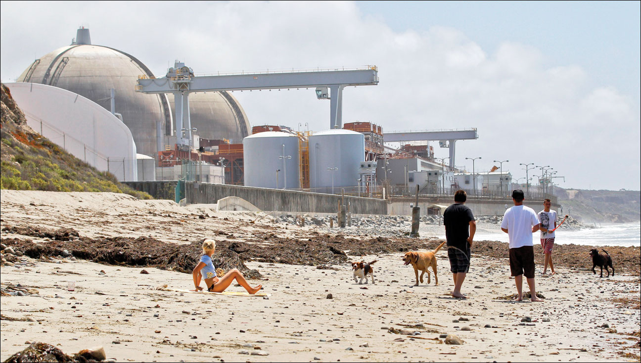People stroll along the beach April 27, 2012, near the San Onofre Nuclear Generating Station in San Onofre, Calif. Two beleaguered reactors were shut down at the San Onofre plant, which hasn't produced electricity since January 2012, when a tiny radiation leak led to the discovery of damage to hundreds of tubes that carry radioactive water. Nuclear Regulatory Commission Chairman Allison Macfarlane said nuclear power plants in the U.S. are safer since the crisis in Japan two years ago; however, they are not trouble-free. (AP file photo by Lenny Ignelzi)