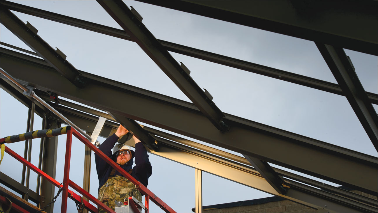 David Hill, an employee of Janco Greenhouses Inc., Elkton, Md., works on the frame for a greenhouse atop Lakeshore Residence Hall on March 12, at the University of Wisconsin-Madison. J.P. Cullen & Sons Inc., Janesville, is overseeing construction of the five-story, 44,200-square-foot building and remodeling of the adjacent Holt Commons. A bill in the Wisconsin Assembly would allow contractors to buy construction materials tax free for projects by nonprofit organizations such as schools, governments and churches. (Staff photo by Kevin Harnack)