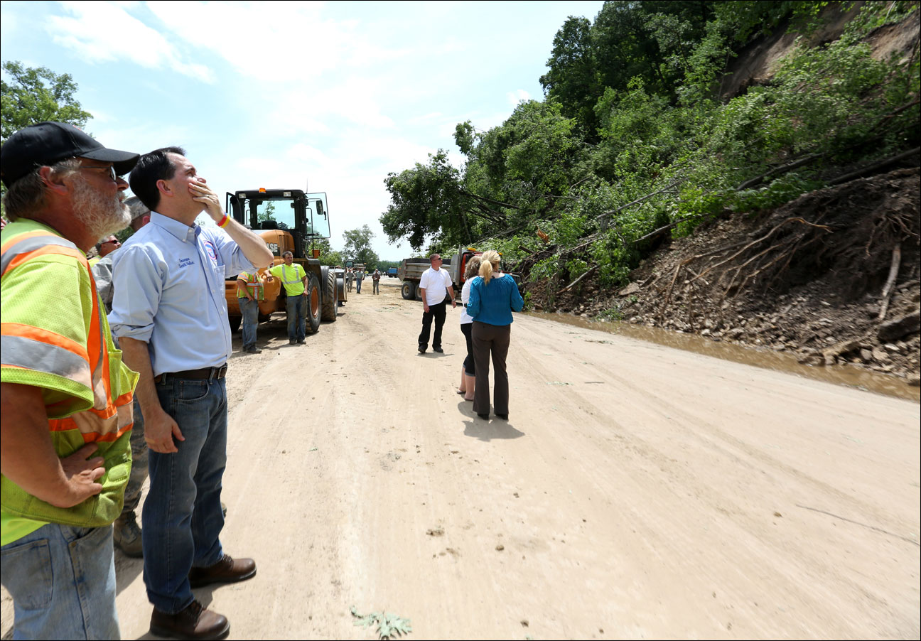 Wisconsin Gov. Scott Walker (second from left) looks at a mudslide along Highway 61 near Boscobel, Wis., Wednesday, June 26, 2013. Gov. Walker toured flood damage in southwestern Wisconsin where homes and businesses were damaged by heavy rain. (AP Photo/Telegraph Herald, Jessica Reilly)