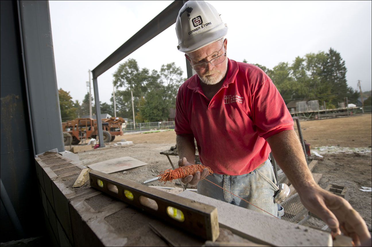Line of sight Bill Wilke, an employee of Corner Stone Construction Co. of Janesville Inc., sets up a string line Oct. 3 while setting precast sill blocks on the exterior ofWeatherStone Church in New Berlin. Magill Construction Co. Inc., Elkhorn, is the general contractor on the project, which is adding a roughly 25,000-square-foot addition for sanctuary offices and classroom space. The project is expected to be complete in mid-March. (Staff photo by Kevin Harnack)