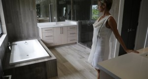 Mara Boccolini, a realtor associate with South Beach Estates, shows the master bathroom in a newly renovated waterfront property on the market during a viewing for brokers, in Miami Beach, Fla. Standard & Poor's releases its S&P/Case-Shiller index of home prices for September and the third quarter on Tuesday, Nov. 25, 2014. (AP Photo/Lynne Sladky)