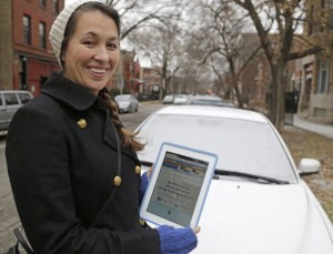 Alexandra Clark, displays the City of Chicago snowplow tracker app on her iPod in front of her car Dec. 19 in Chicago. (AP photos by M. Spencer Green)