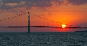 the sun sets over the Mackinac Bridge and the Mackinac Straits as seen from Lake Huron. The bridge is the dividing line between Lake Michigan to the west and Lake Huron to the east. Michigan's attorney general and chief environmental regulator issue a report Tuesday, July 14, 2015 on the safety of oil pipelines, including one stretching beneath an ecologically sensitive area linking Lakes Huron and Michigan. (AP Photo/Al Goldis, File)