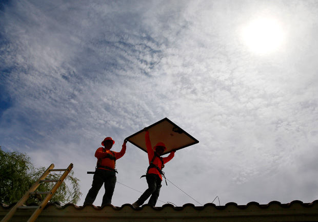 Electricians install solar panels on a roof for the Arizona Public Service company in Goodyear, Ariz., in July. Wind turbines and solar panels accounted for more than two-thirds of all new electric generation capacity added to the nation's grid in 2015. (AP File Photo/Matt York)