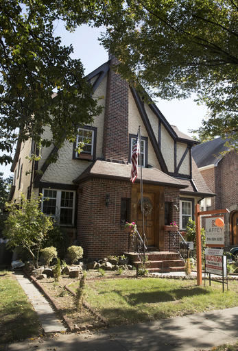 This Tuesday, Oct. 18, 2016 photo, shows the exterior of a house in the Jamaica Estates neighborhood of the Queens borough of New York, where Republican presidential candidate Donald Trump spent his early childhood. Trump's first boyhood home in New York City is going on the auction block with an opening bid of $849,000. (AP Photo/Mary Altaffer)