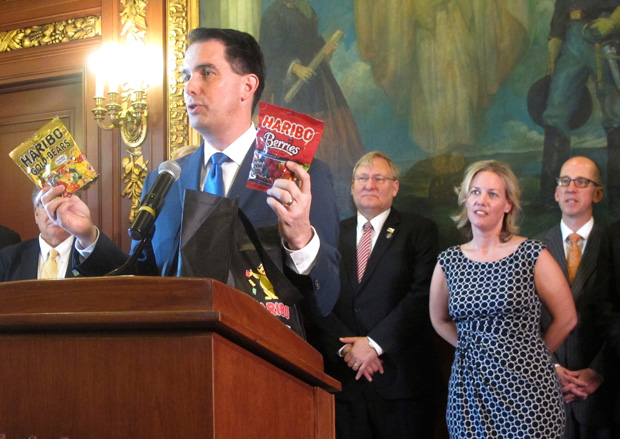 Gov. Scott Walker holds up two bags of Haribo candy on Thursday while announcing the German-based company would be building its first North American manufacturing plant in southeast Wisconsin. Walker's latest budget proposal slashes wages for blue-collar, middle-class construction workers and does nothing to sustain transportation funding. (AP Photo/Scott Bauer)