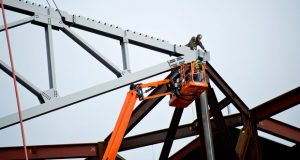 Employees with Janesville-based J.P. Cullen & Sons secure the first section of roof truss on the new Milwaukee Bucks arena on Tuesday. The arena is on track to be complete for the 2018-19 NBA season. (Staff photo by Kevin Harnack)