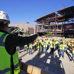 Ryan Olsen, safety manager for Mortenson Construction, leads workers as they warm up and stretch. (AP Photo/Carrie Antlfinger)