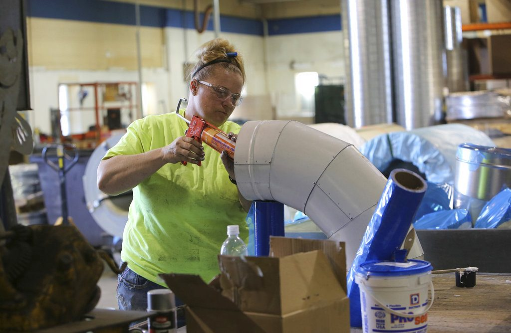 ADVANCE FOR MONDAY, MAY 28 AND THEREAFTER  Brandi Johnson, sheet metal worker, caulks PVC piping in the shop at H&H Industries in Madison, Wis., Wednesday, April 25, 2018. (Michelle Stocker/The Capital Times via AP)