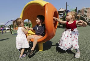 The three-year-old twins Maisie, left, and Coraline attempt to spin their brother, Desmond, 7, in a cozy hideaway at Brittingham Park's playground on July 23 in Madison. (Amber Arnold)/Wisconsin State Journal via AP)