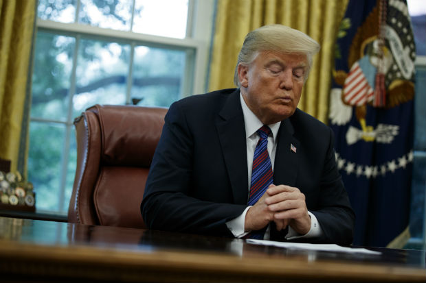 "President Donald Trump talks on the phone with Mexican President Enrique Pena Nieto, in the Oval Office on Monday. Trump is announcing a trade ""understanding"" with Mexico that could lead to an overhaul of the North American Free Trade Agreement. (AP Photo/Evan Vucci)"