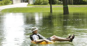 Joman Schachter makes his way down the Yahara River in an inner tube at Tenney Park in Madison, Wis., Thursday, Aug. 23, 2018. Schachter hoped to float all the way home, which is near Olbrich. Madison city officials are warning residents that rising lake levels will lead to flooding, including main roads in and out of the city center around the state Capitol. (Amber Arnold/Wisconsin State Journal via AP)