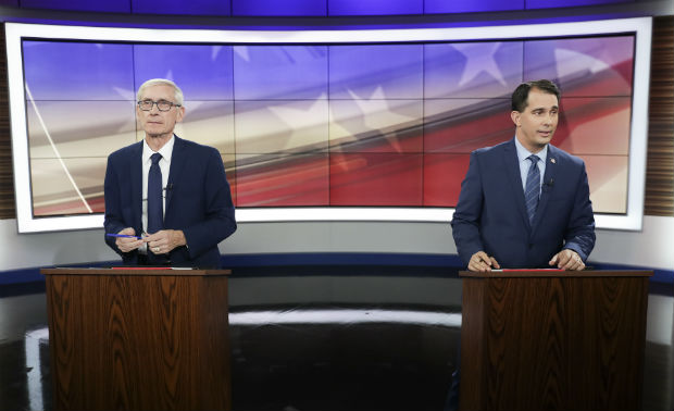 Tony Evers, the Democrat running for governor in Wisconsin, left, and Gov. Scott Walker, a Republican, take part in a 10-minute media event before the start of their gubernatorial debate hosted in Madison, Wis., Friday, Oct. 19, 2018. (Steve Apps/Wisconsin State Journal via AP)