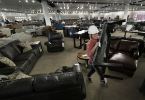 Jenny Gagan, an assistant buyer at the new WG&R store in Grand Chute, sets up furniture for a photography shoot on Oct. 18. (Dan Powers/The Post-Crescent via AP)