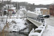 The Baraboo River runs through downtown Rock Springs on Jan. 1. The river rose above its banks in August to flood the village's downtown, damaging a nearby library. (Amber Arnold/Wisconsin State Journal via AP)
