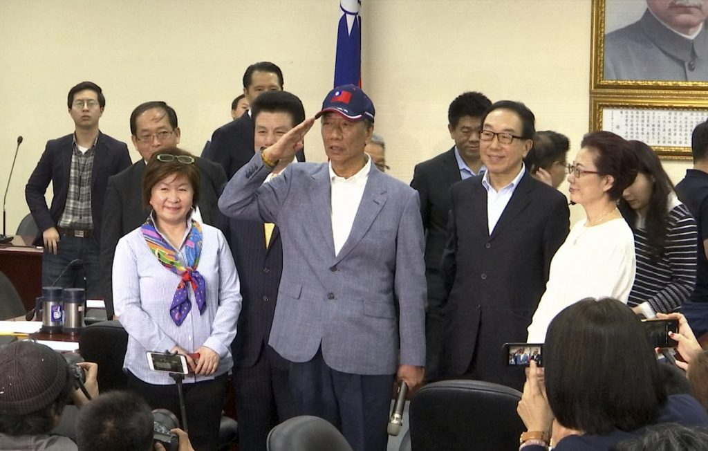 In this image made from video, Terry Gou, center, the head of the world's largest electronics supplier, Foxconn, gestures during a press conference at the Nationalist Party's headquarters in Taipei, Wednesday, April 17, 2019. Gou said Wednesday he plans to run for president of Taiwan, bringing his pro-business and pro-China policies to what is expected to be a crowded field for next year's election. (AP Photo/Johnson Lai)
