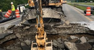 Construction crews work on Wednesday on a sinkhole site on the eastbound lanes of Interstate 265 in Clarksville, Indiana. State transportation officials say a sinkhole that opened up overnight on a southern Indiana highway has forced them to close part of the highway. (Indiana Department of Transportation via AP)