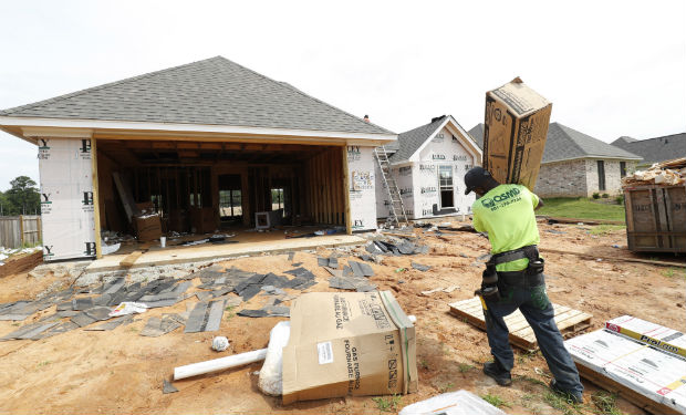 A worker carries supplies on June 19 for a new house in a Brandon, Mississippi. The U.S. Department of Commerce reported Tuesday that sales of new houses Sales of new U.S. houses slumped by 7.8% in May. (AP Photo/Rogelio V. Solis)