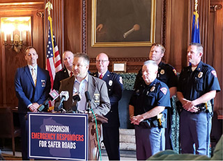 Brandon Ferrell of the Wisconsin Troopers Association, flanked by representatives of the Wisconsin Professional Police Association, Badger State Sheriffs' Association and Professional Fire Fighters of Wisconsin, argue at a press conference on Tuesday at the state Capitol that public safety is being put at risk because of poor road conditions. Ferrell and other speakers called on the state Legislature to pass a long-term roads plan but stopped short of advocating for any particular proposal. Gov. Tony Evers has called for raising the state's gas tax by 8 cents a gallon as part of his plan to increase road funding by $608 million over two years. But Senate Majority Leader Scott Fitzgerald, a Republican, said last week the gas-tax hike would be rejected. (Photo submitted by Roger Putnam III)