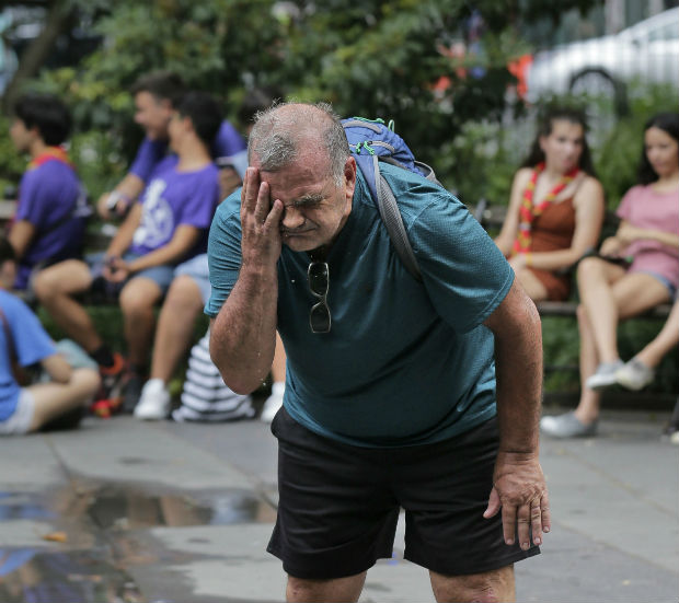 Russ Wilson splashes water on his face from a fountain in New York on Wednesday. The heat wave that has been roasting much of the U.S. in recent days is just getting warmed up, with temperatures expected to soar to dangerous levels through the weekend. (AP Photo/Seth Wenig)