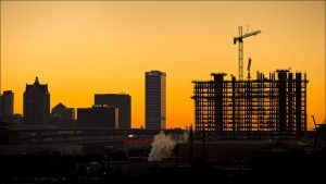 A crane looms over Milwaukee near the Potawatomi Hotel and Casino in August 2013. Officials in both Wisconsin and Minnesota have been trying in recent years to crack down on wage theft and worker misclassification, abuses to which immigrants are particularly susceptible.