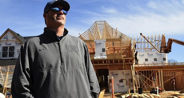 Todd Polifka of Custom One Homes Construction, stands on March 31 before one of the homes he is building in the Amberwood housing development in Inver Grove Heights, Minnesota. Polifka wonders if this will be a lost year for the housing industry. Home builders say the coronavirus outbreak will push back construction starts by four months — a delay that could wipe out their peak building months off the calendar. (Scott Takushi/Pioneer Press via AP)
