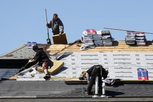 FILE - In this April 2, 2020 file photo, roofers work on April 2 to remove and place new shingles on a house in Warren, Michigan. U.S. home-building activity collapsed in March as the coronavirus spread. (AP Photo/Paul Sancya, File)