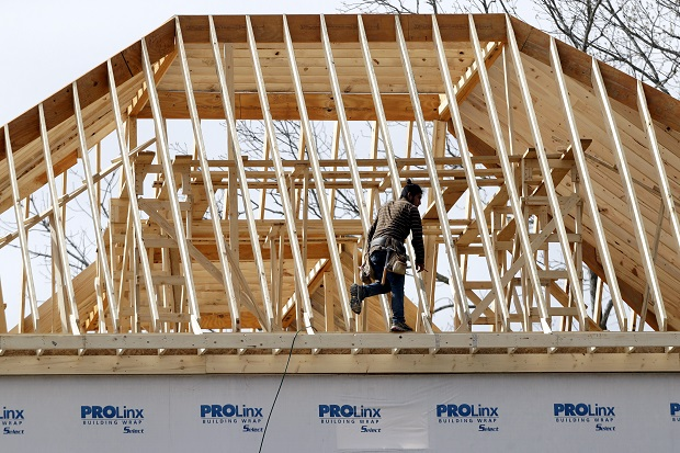 A construction worker walks along a roof on a new home in Nashville, Tennessee, on March 25.  The Commerce Department reported on Wednesday  that new homes were started at a seasonally adjusted annual rate of 974,000 last month after steep declines in April and March. (AP Photo/Mark Humphrey)