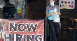A customer wears a face mask on Sept. 2 as he carries his order past a now hiring sign at a restaurant in Richardson, Texas.  The number of Americans seeking unemployment benefits fell slightly last week to 751,000, a still-historically high level that shows that many employers keep cutting jobs amid the accelerating pandemic. (AP Photo/LM Otero, File)