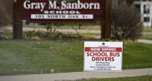 A hiring sign stands outside Gray M. Sanborn Elementary School in Palatine, Illinois, in November. In the week leading up to Wednesday, the number of Americans seeking unemployment benefits had fallen by 89,000 to a still-elevated figure of 803,000, evidence that the job market remains under stress nine months after the coronavirus outbreak sent the U.S. economy into recession and caused millions of layoffs.  (AP Photo/Nam Y. Huh)